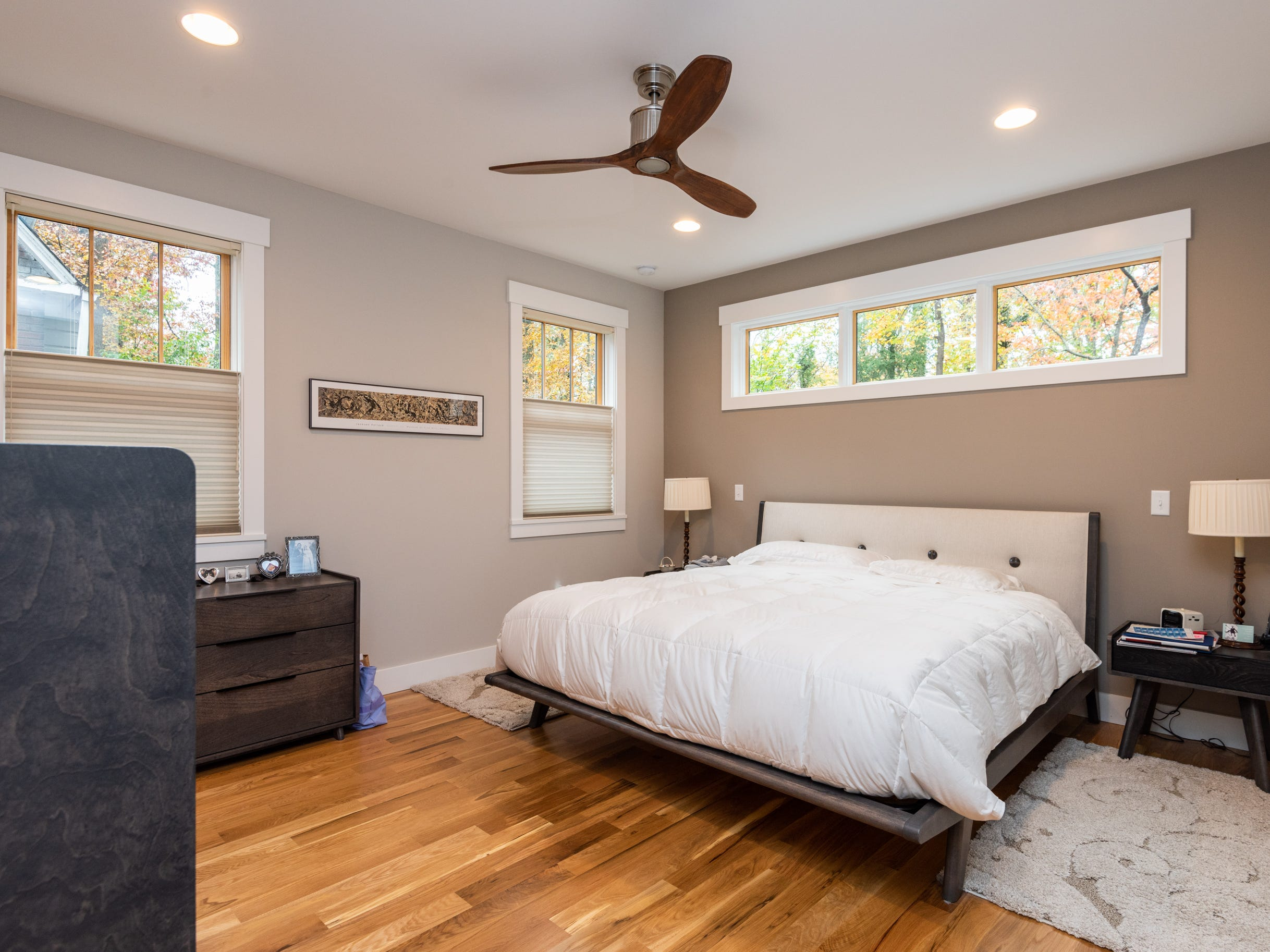 The master bedroom is well lit by windows that also provide privacy.