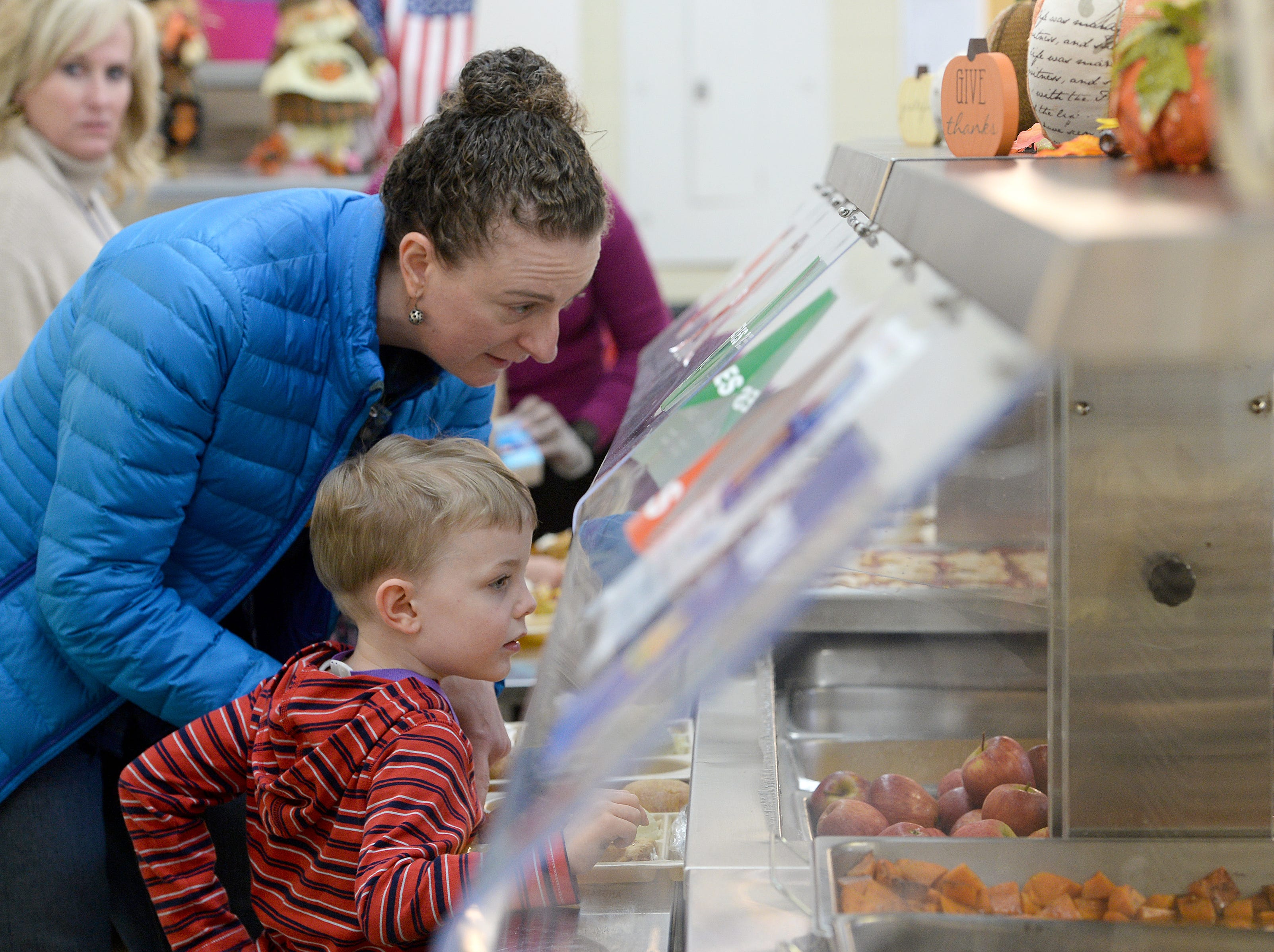 Audrey Gurin and her son, Simon, 5, check out their fruit options in line as they eat a special Thanksgiving-style lunch together at Ira B. Jones Elementary School on Nov. 14, 2018. Asheville City Schools served a special meal at all of their schools to celebrate the holiday.