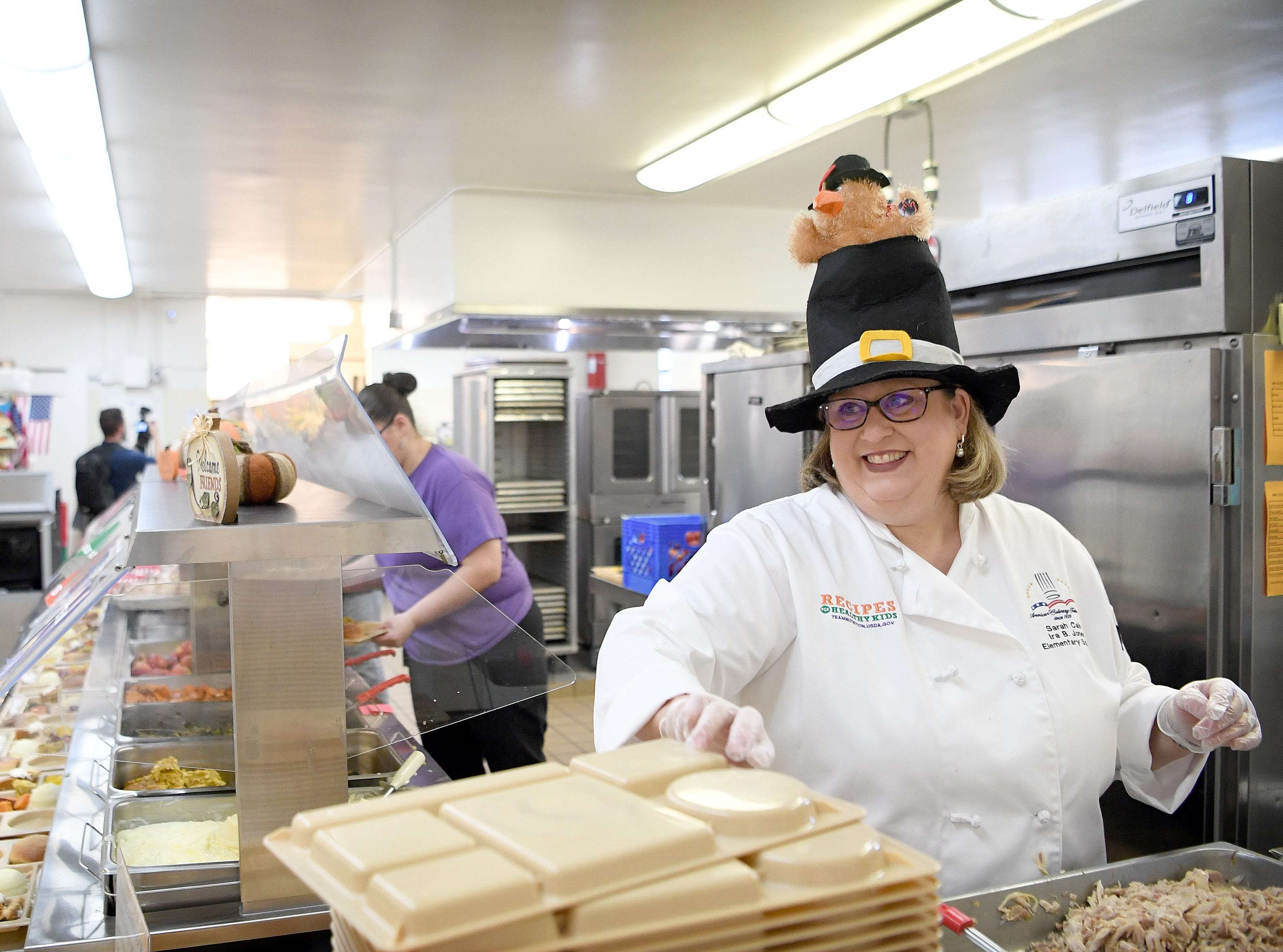 Sarah Cain, principal of Ira B. Jones Elementary School dons a festive hat as she helps serve lunch to her students and their parents during a Thanksgiving lunch at the elementary school on Nov. 14, 2018. Asheville City Schools served a special meal at all of their schools to celebrate the holiday.