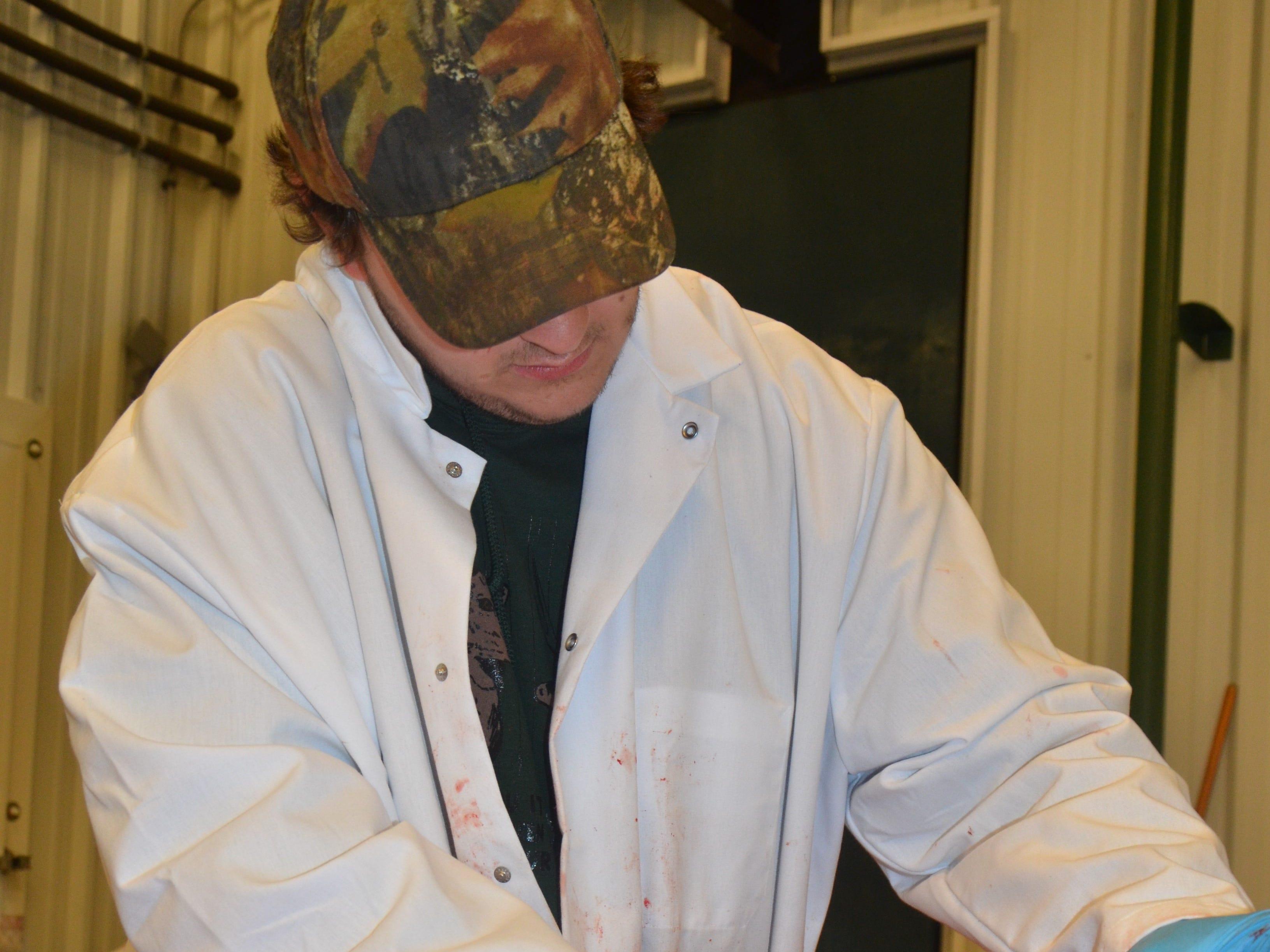 Justen Knight debones venison at Whitetail Farms in Olivet.