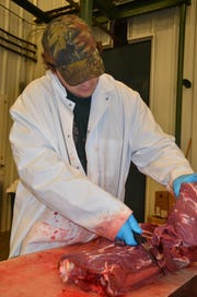 Justen Knight debones venison at Whitetail Farms in Olivet.