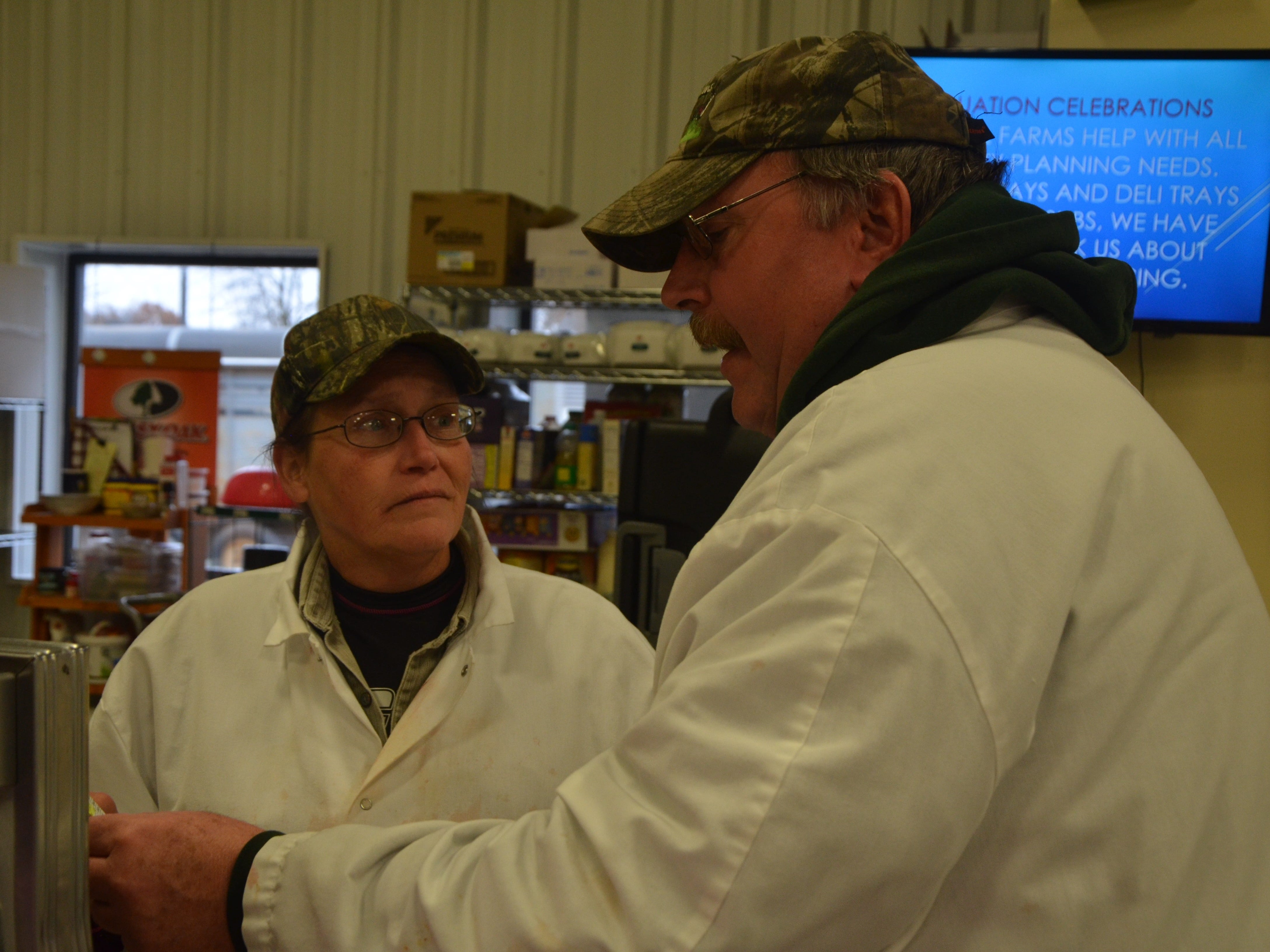 Whitetail Farms owner Greg Saltzman goes over an order with Cheryl Foster.