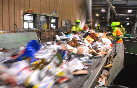 Recyclables whiz past on a conveyor belt inside Waste Management Recycling Brevard in Cocoa.