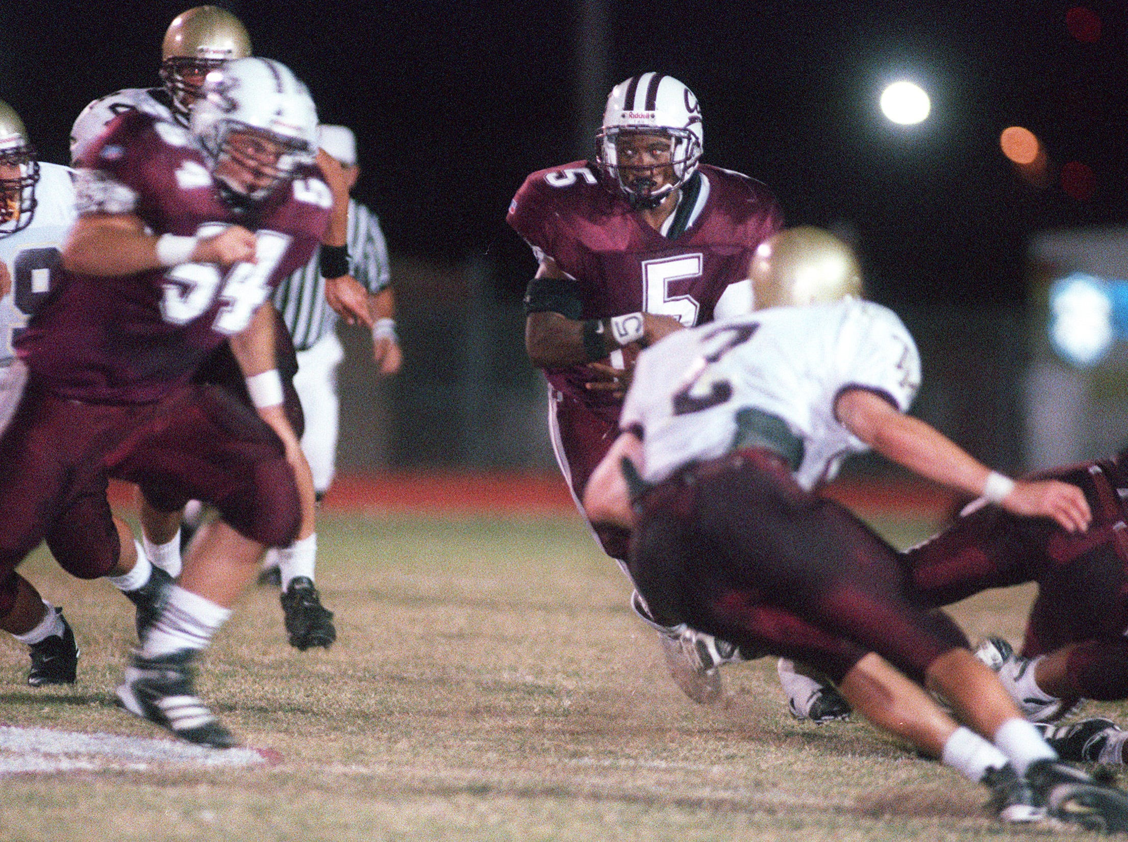 Calallen's Francis Garner #54 (left) charges T-M's Travis Hardcastle #2 (right) to allow room for Calallen's Victor Price to run during Friday night football game action at Calallen. (photo by michelle christenson 10/16/98)