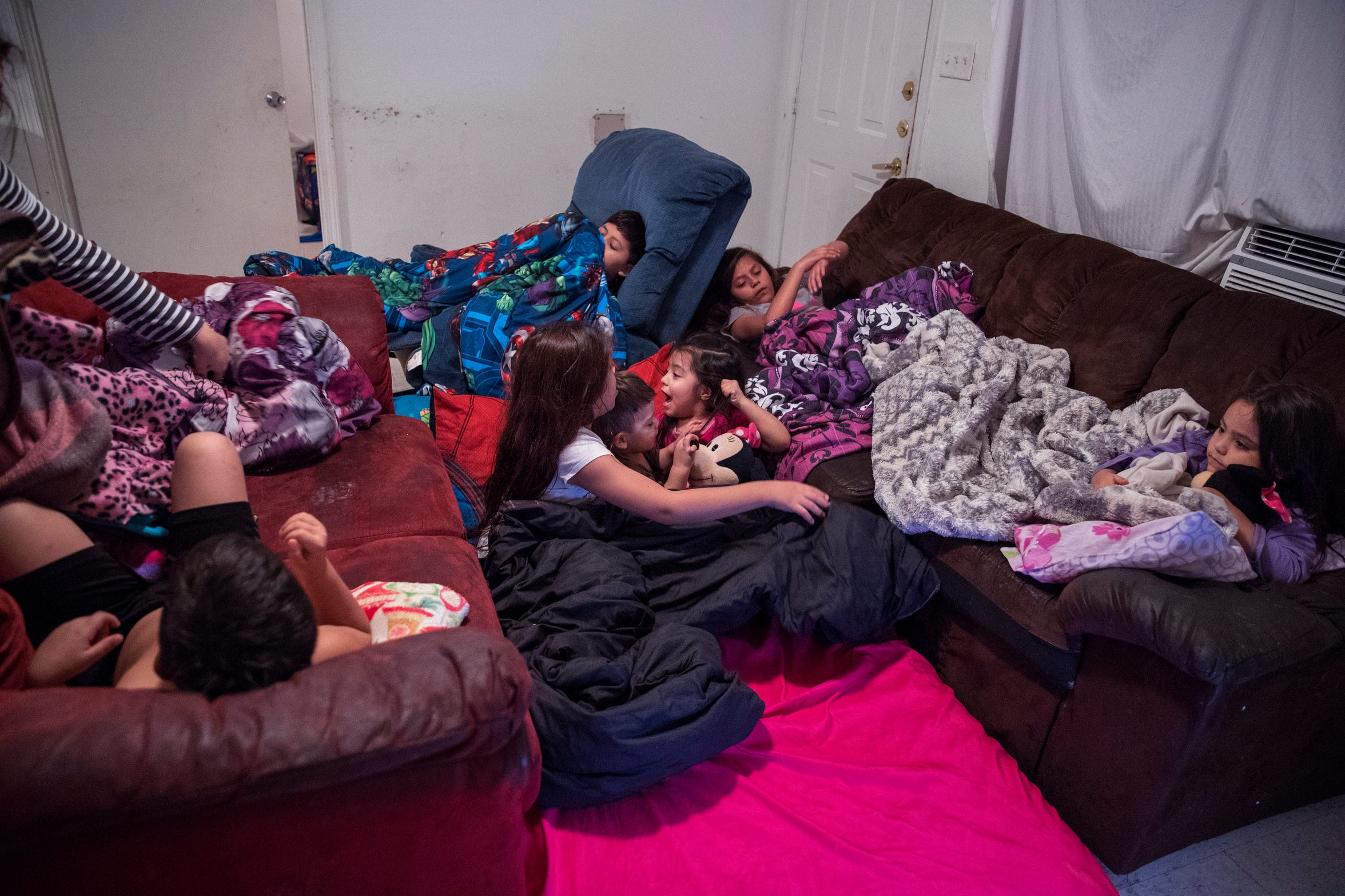Deanna Martinez gets her kids ready for bed inthe living room to at Rincon Point Apartments in Taft in October. The family has been living in the living room since the air condition went out and the company failed to provide air conditioning window units for the children's bedrooms.