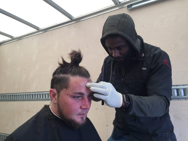 Sean McCann sits for a haircut by Rob Lane at a resource fair for homeless people in Camden.