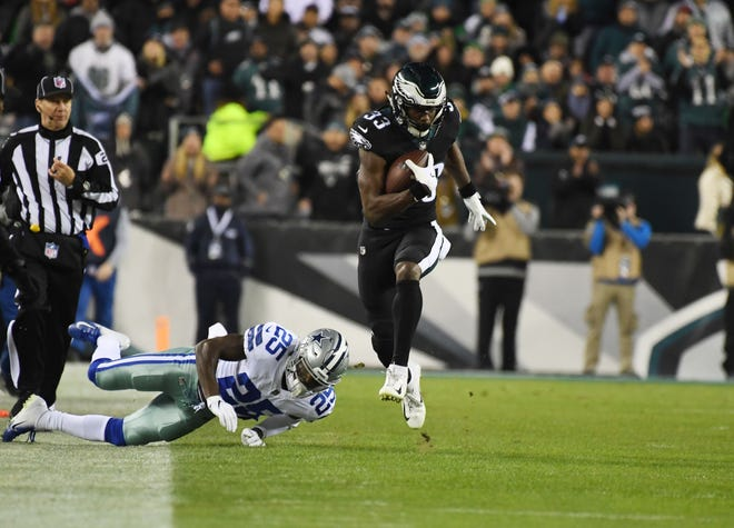 Eagles running back Josh Adams (33) gets away from Cowboys safety Xavier Woods during Sunday night's loss.