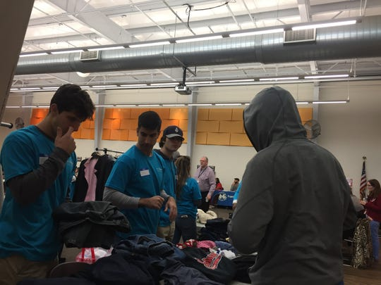 A homeless man looks through clothes at Threads for Success' table at a resource fair in Camden recently.
