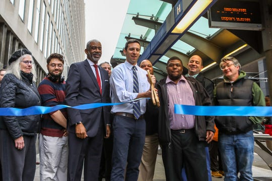 Councilman P.G. Sittenfeld and other officials stand together and cut the ribbon for a bus-only lane on Main street in downtown Cincinnati on Monday Nov. 5, 2018.