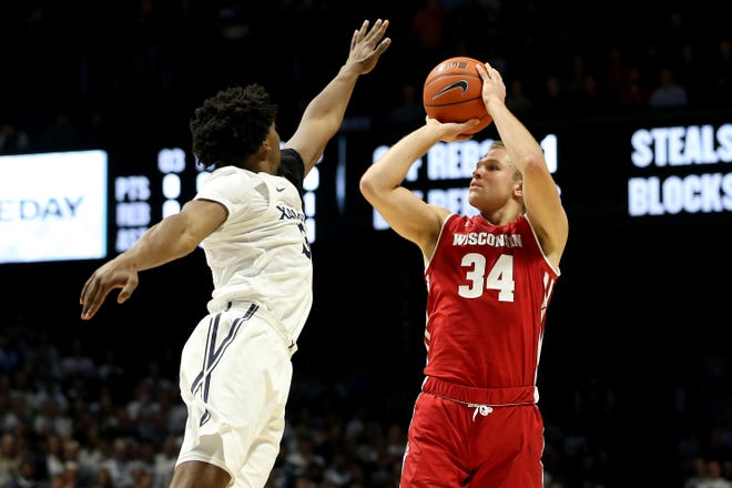 Wisconsin Badgers guard Brad Davison (34) rises for a shot as Xavier Musketeers guard Quentin Goodin (3) defends in the first half during a college basketball game between the Wisconsin Badgers and the Xavier Musketeers, Tuesday, Nov. 13, 2018, at the Cintas Center in Cincinnati.