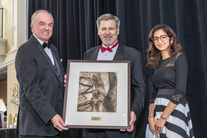 RVCC President Michael J. McDonough, left, and RVCC student Raina Naveed present Raymond L. Hughes II, president, New Jersey Risk Managers & Consultants, Inc., and president, Hughes-Plumer & Associates, with an original etching created by RVCC alum Elizabeth Mitchell of Pittstown. Hughes was honored as a Community Leader at RVCC's Golden Harvest Gala.