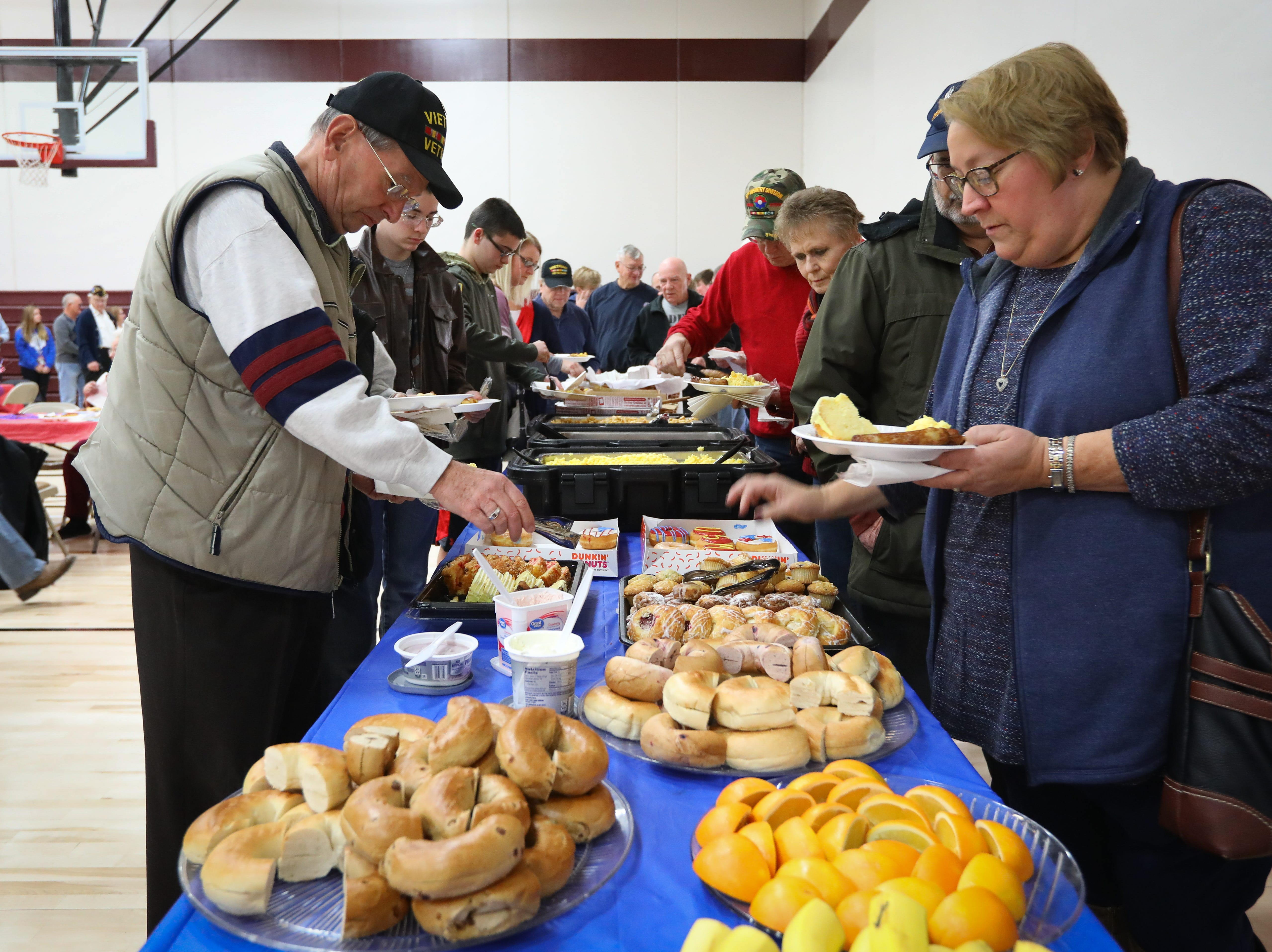 Mervin Vaughn, left, an Army veteran, gets food during Veterans Day Breakfast at Northview Middle School on Wednesday, Nov. 14, 2018 in Ankeny, Iowa. Middle school students hosted the veterans to share their gratitude before an assembly.