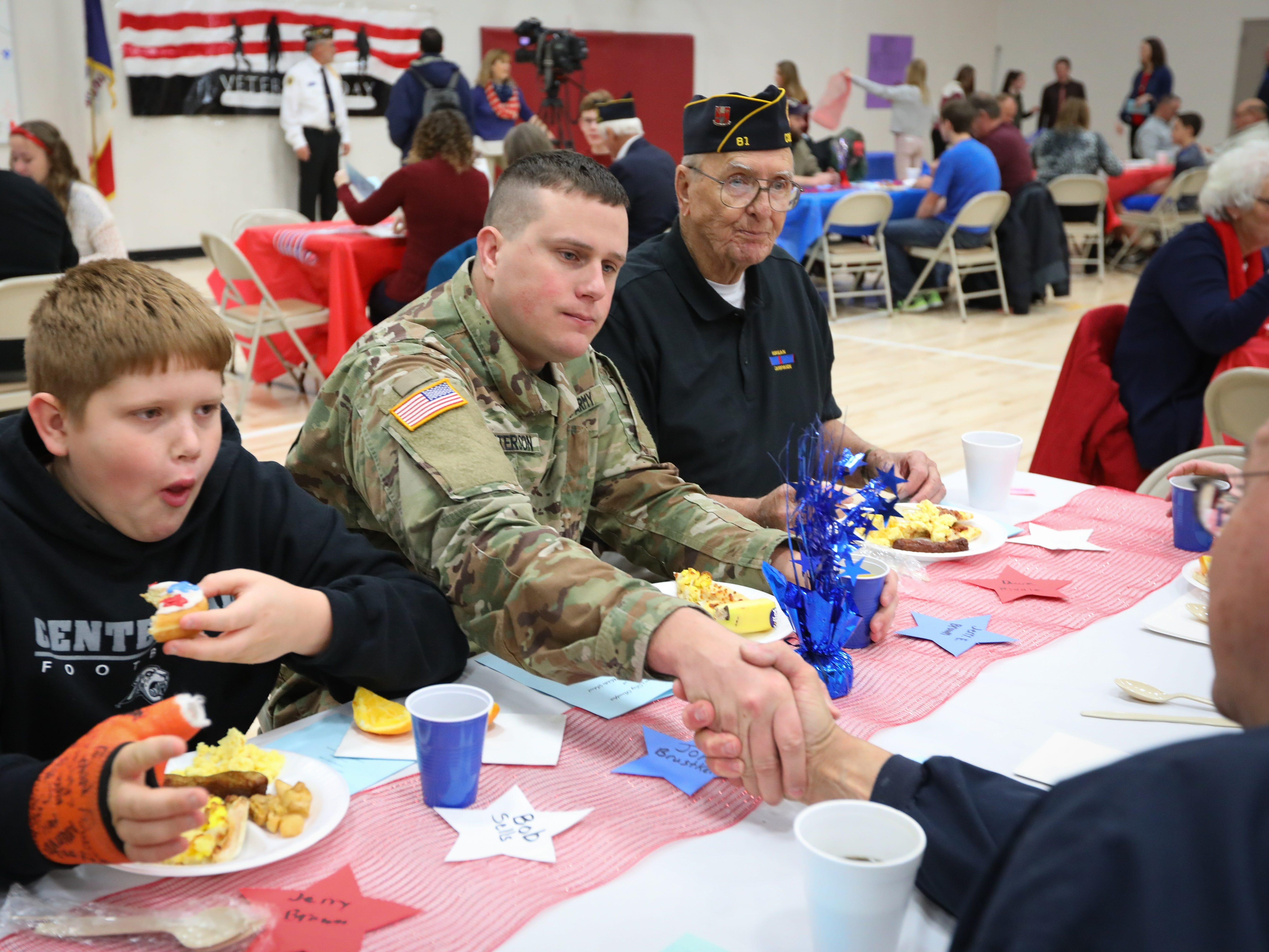 Kyle Patterson, center, an Army veteran, shakes hand with another veteran during a Veterans Day Breakfast at Northview Middle School on Wednesday, Nov. 14, 2018 in Ankeny, Iowa. Middle school students hosted the veterans to share their gratitude before an assembly.