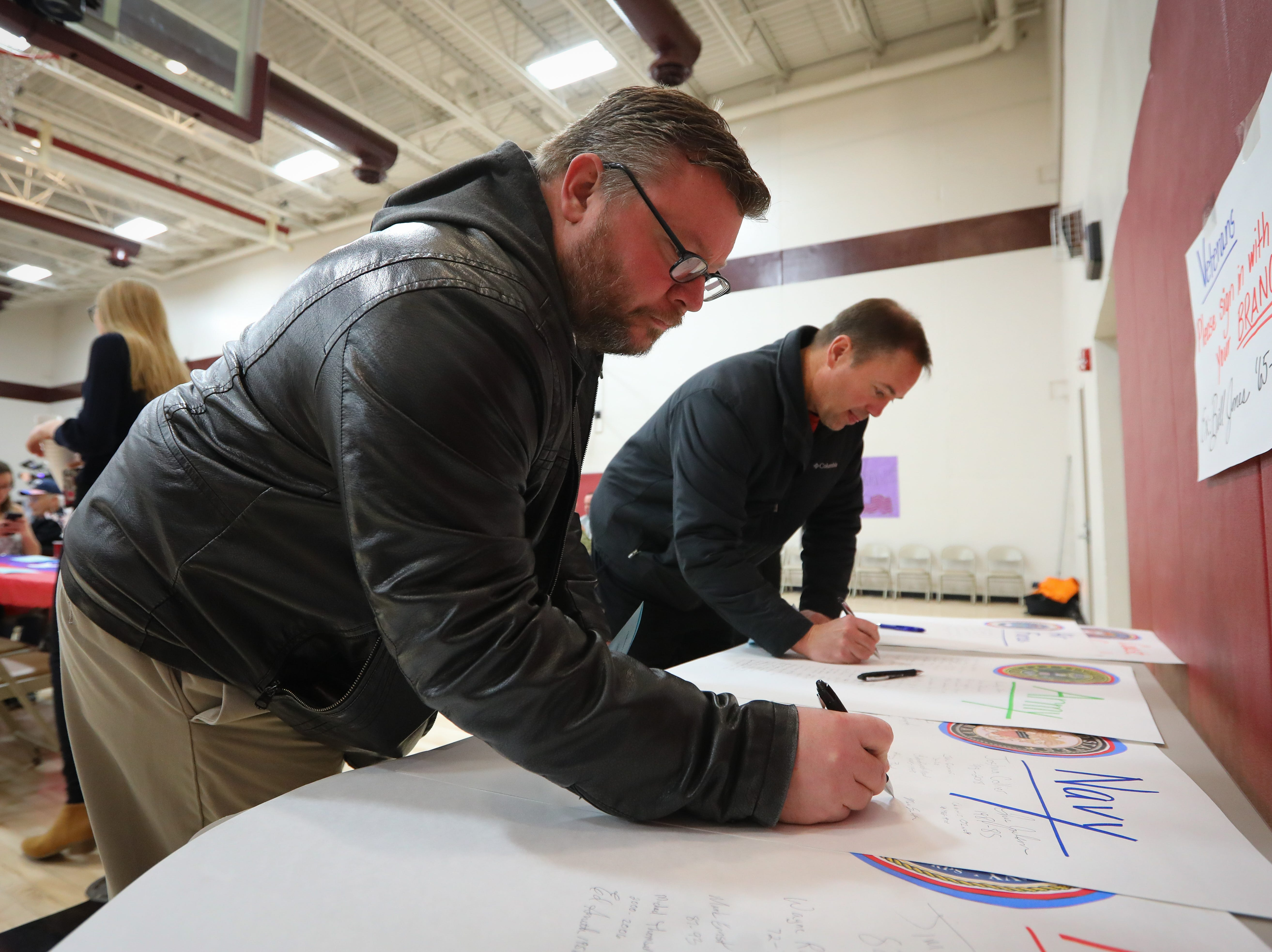 Marc Smith, a naval veteran, signs his name during Veterans Day Breakfast at Northview Middle School on Wednesday, Nov. 14, 2018 in Ankeny, Iowa.