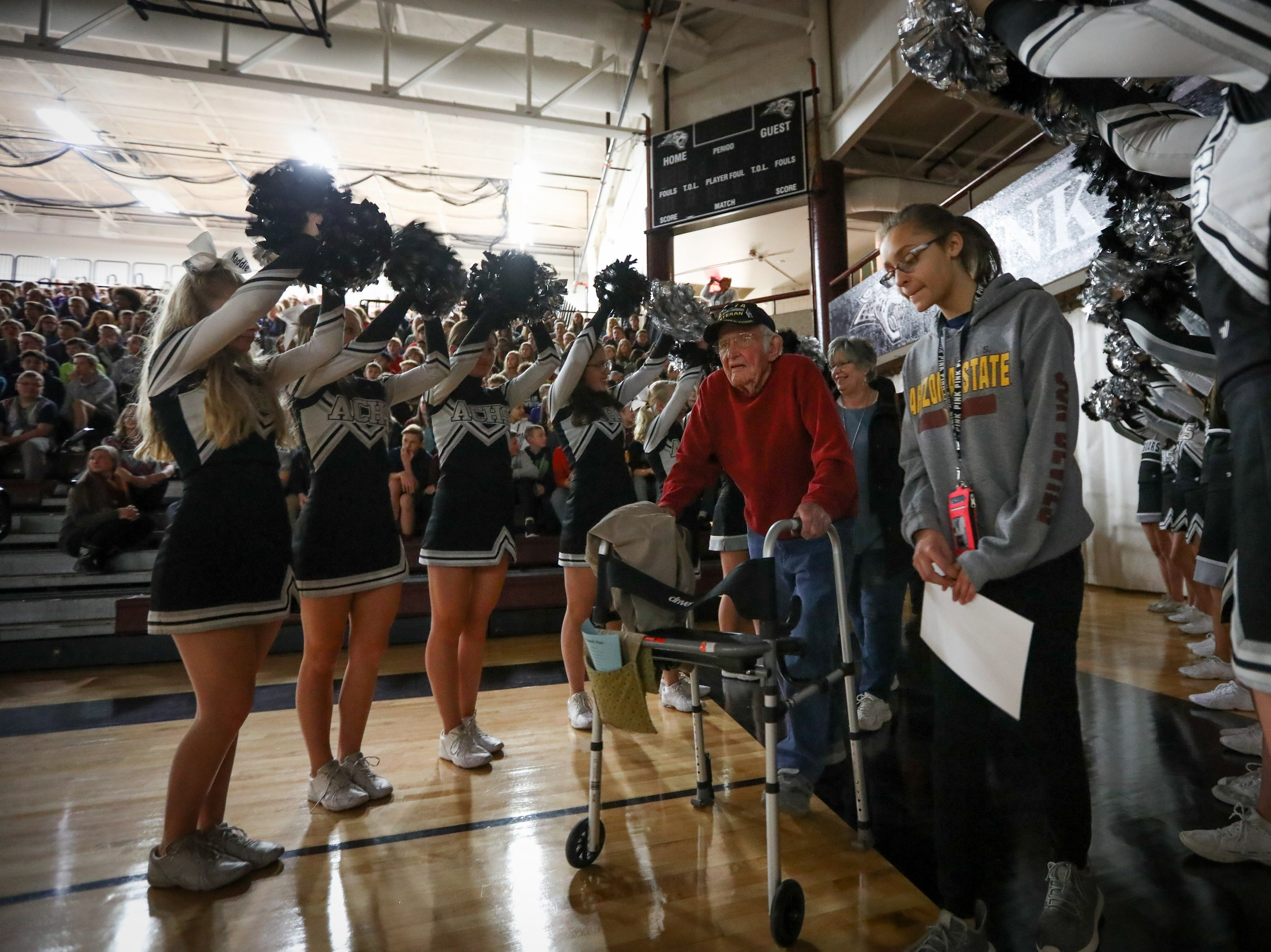 Paul Friedel, from the Air Force, enters the school gym through a line of cheerleaders during Veterans Day Breakfast at Northview Middle School on Wednesday, Nov. 14, 2018 in Ankeny, Iowa.