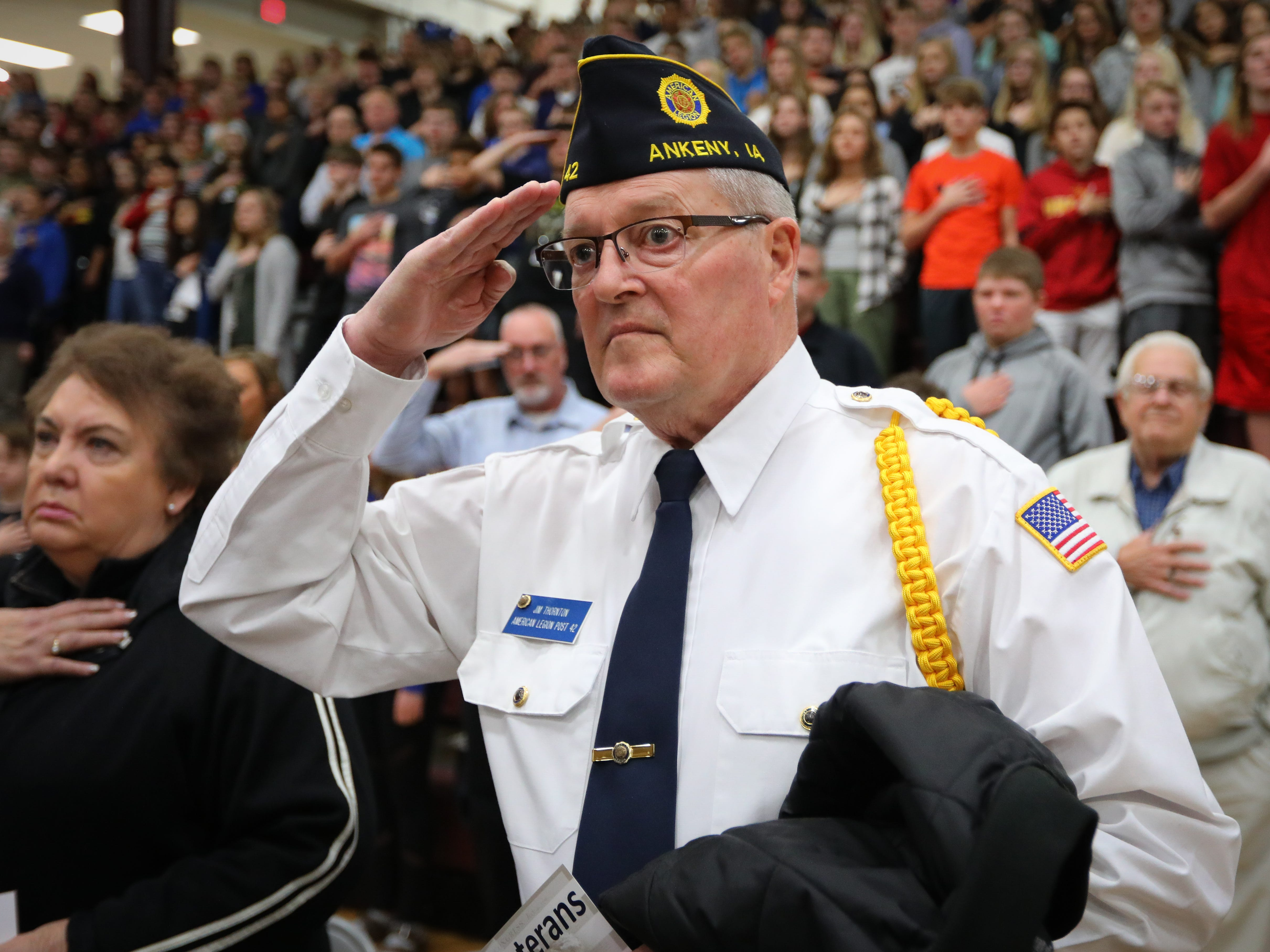 Jim Thorton, from the Navy, salutes during the national anthem during the Veterans Day Breakfast at Northview Middle School on Wednesday, Nov. 14, 2018 in Ankeny, Iowa. Middle school students hosted the veterans to share their gratitude before an assembly.