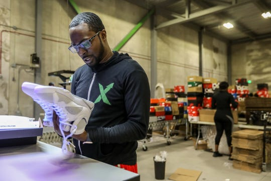 Antonio Gray, 29, of Detroit , worked as a sneaker salesman for six years before becoming a authenticator at Stock X, where he looks over a pair of Jordans at their new authentication center in Detroit on Tuesday, July 3, 2018. Stock X  has created day trading for consumer goods and is doing $2 million in sales daily.