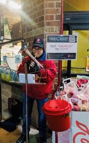 Some volunteers showcase their musical talents beside storefront red kettles to create holiday spirit and encourage donations.