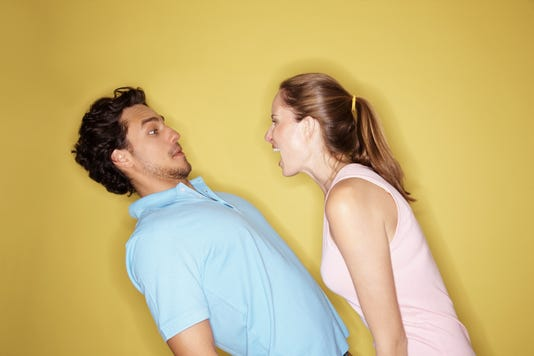Angry Woman Shouting At A Man Against Yellow Background