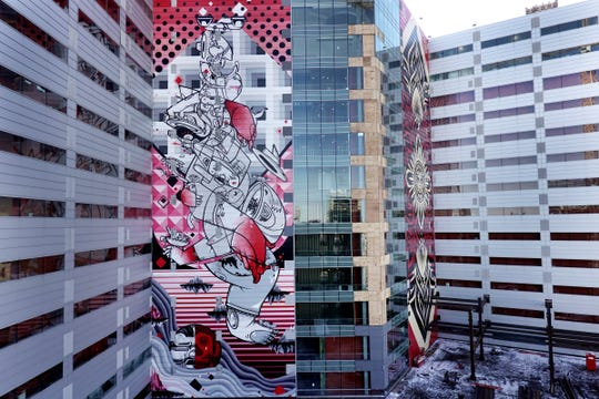 Balancing Act, a mural by How & Nosm on One Campus Martius building in Detroit on Wednesday, Nov. 14, 2018. A large mural by street artist Shepard Fairey is seen on the right.
