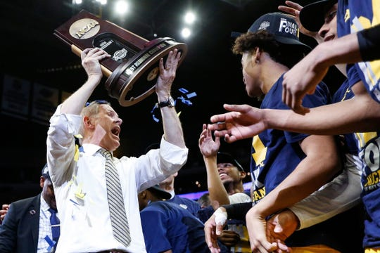 Michigan coach John Beilein celebrates and raises the West Region championship trophy after defeating Florida State in the Elite Eight in the NCAA tournament in Los Angeles, Calif., Saturday, March 24, 2018.