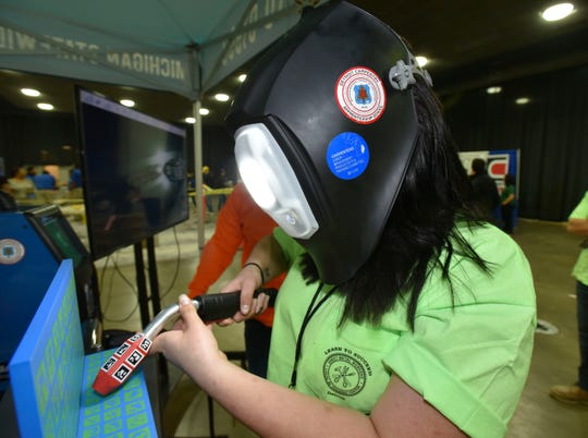 Local 80 sheet metal apprentice Alex Elliott, of Wixon, tries her hand on a virtual-welding simulator at the Michigan Regional Council of Carpenters and Millwrights School display Wednesday at Cobo Center.