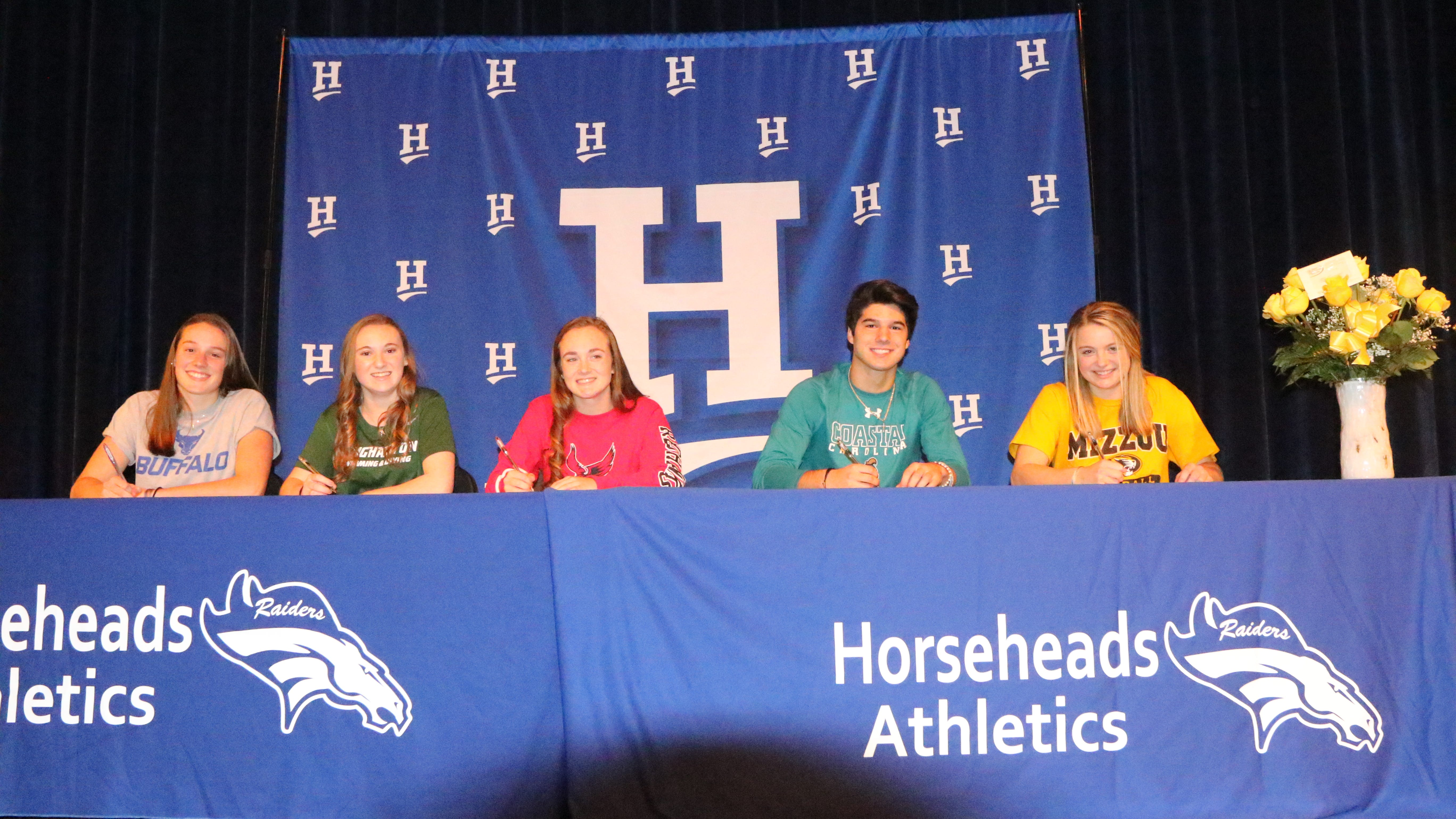 Horseheads athletes, from left, Maddy Rogan, Chloe Peterson, Skyler Roberts, Mike Limoncelli and Kendal Cook participate in a signing ceremony Nov. 14, 2018 at the Horseheads High School auditorium.