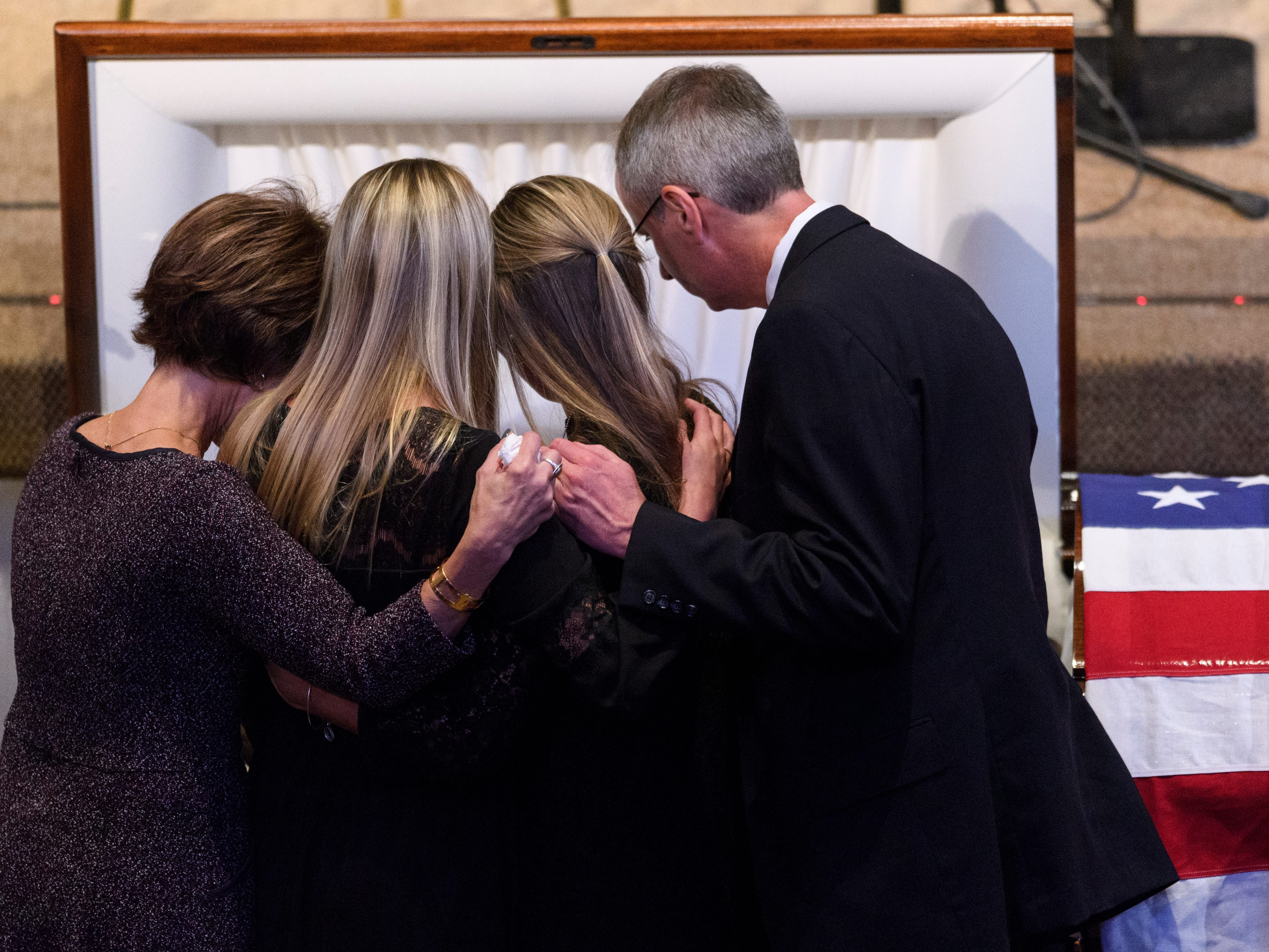 "Army Sgt. Drew Watters' parents Karen Watters, left, and Scott Watters, right, embrace their daughters Ellen Watters and Colleen Watters, center, as they say goodbye to him before the casket is closed during a ""Celebration of Life"" ceremony held for him at Christian Fellowship Church in Evansville, Ind., Wednesday, Nov. 14, 2018."