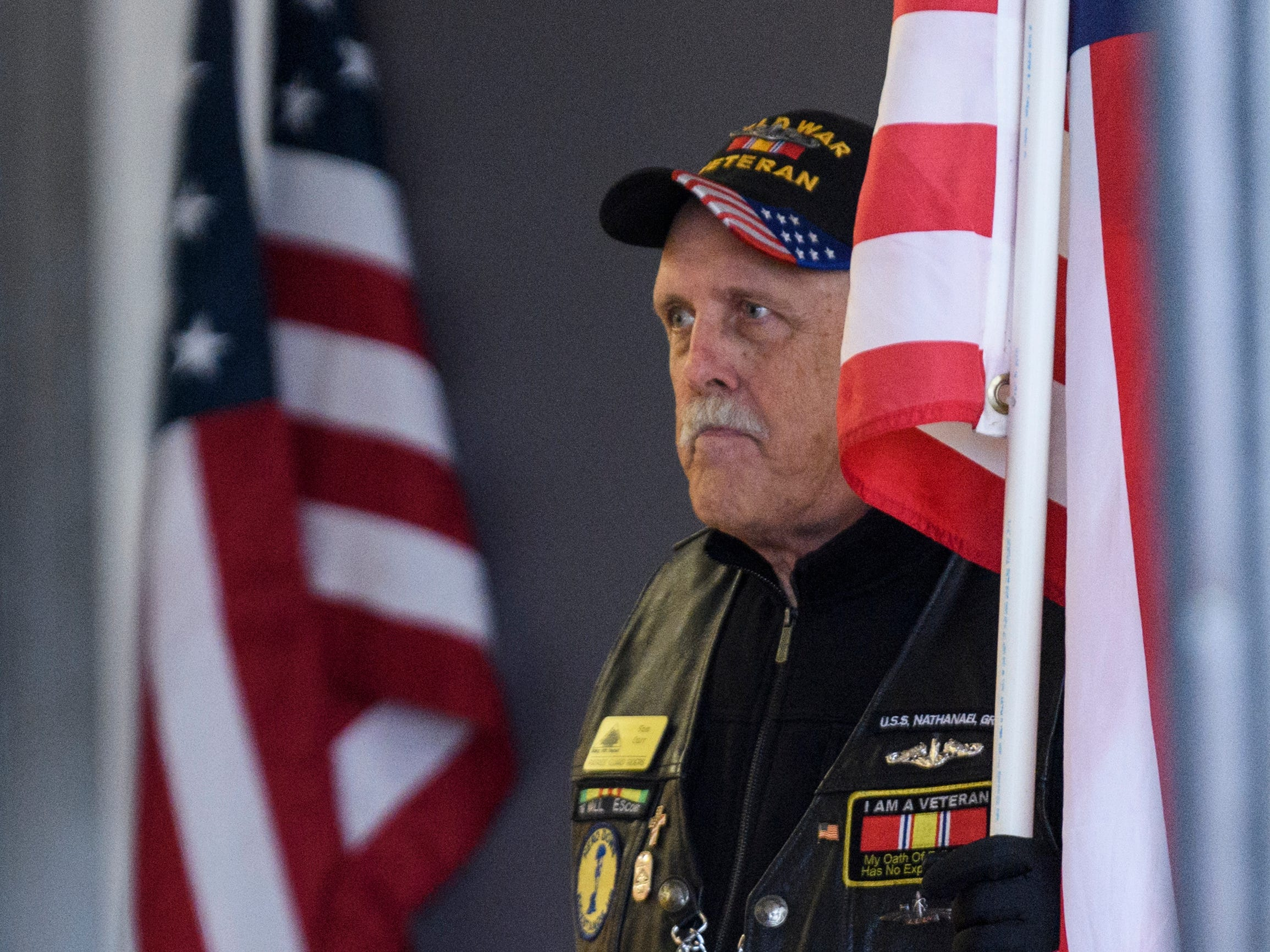 "Tom Carr of the Southwest Indiana Patriot Guard Riders holds an American Flag in the entryway of Evansville's Christian Fellowship Church during a visitation held for Army Sgt. Drew Watters, Tuesday afternoon, Nov. 13, 2018. ""Honor and respect, that's our motto,"" Carr said of the volunteer organization. The group, which includes military veterans and civilians, attend memorial services at the request of deceased soldiers' or veterans' family."