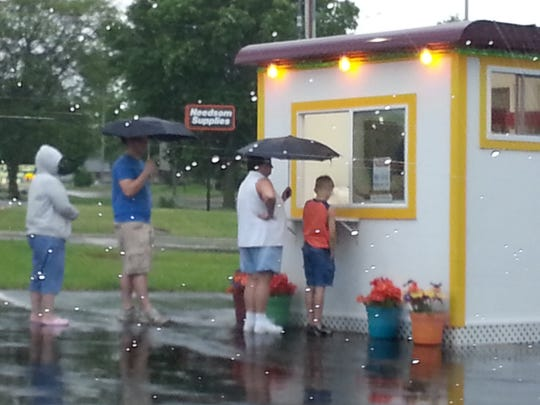 People line up even in the rain to get popcorn.  The photo was taken after the stand was purchased and operated at Tuckers, 927 S. Main Street, where it remains today.