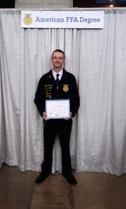 Garrett Joseph holds his American FFA Degree.