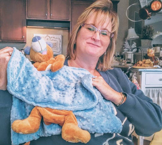 Christina Cleveland shows off a blanket she made with donated fabric and a stuffed animal placed in front of the Watts' home in Frederick.