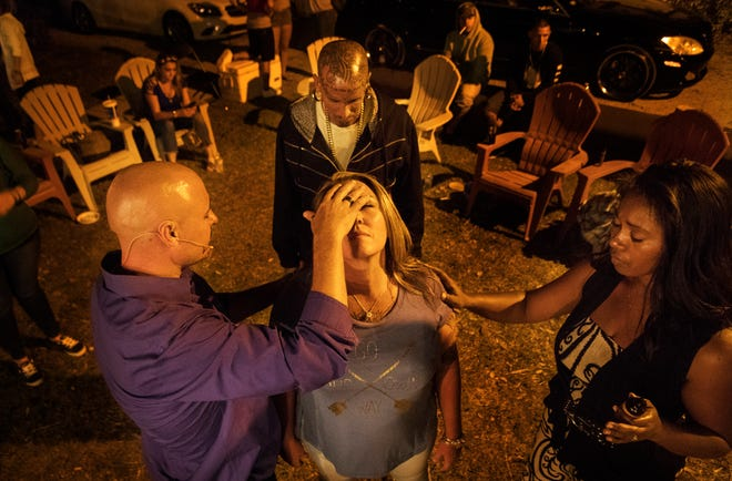 Craig Hunt and his wife Sheanna Hunt pray over Recovering Lives sober home resident Julie Kovach during a Light Xplosion Ministry service at the homes recently. Recovering Lives is a home for those overcoming addiction.