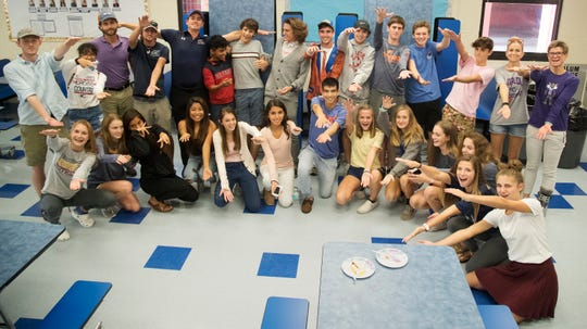 Estero High School's Hugh Brittenham, center, his teammates and coaches celebrate his signing a letter of intent on Wednesday during a National Signing Day event at Estero High School. Brittenham will run track at the University of Florida.