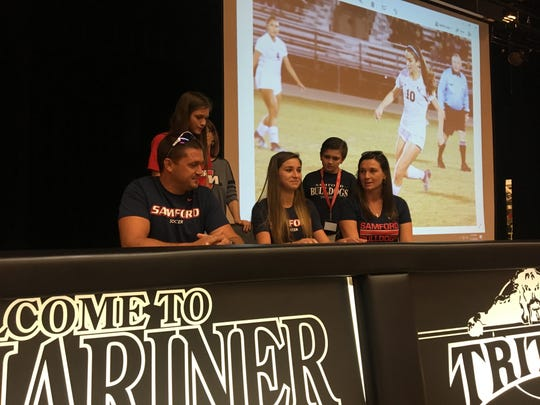 Taylor Young of Mariner High School signs her letter of intent to play soccer at Samford University in Birmingham, Alabama, as her family watches Wednesday.