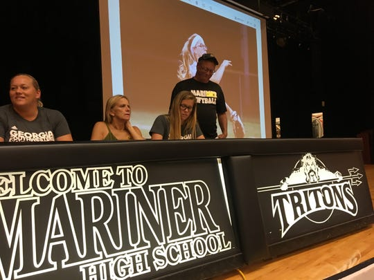Hannah Holloway of Mariner High School signs her letter of intent to play softball at Georgia Southwestern State University in Americas, Georgia, as her family watches Wednesday.