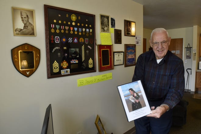 Ret. U.S. Army 1st Sgt. Lloyd Nimmer of Kewaunee shows off a surprise Veterans Day gift from granddaughter Karlee Horlacher -- a pair of military photos of Nimmer that she held while she posed on Omaha Beach in Normandy, a placehe would have liked to visit. The wall behind Nimmer is covered with significant items and mementos from his 33 years of service.