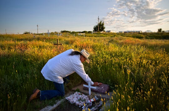 FILE--In this July 14, 2018, file photo, Kenny Still Smoking touches the tombstone of his 7-year-old daughter, Monica, who disappeared from school in 1979 and was found frozen on a mountain, as he visits her grave on the Blackfeet Indian Reservation in Browning, Mont. A study released by a Native American non-profit says numerous police departments in cities nationwide are not adequately identifying or reporting cases of missing and murdered indigenous women. (AP Photo/David Goldman, file)