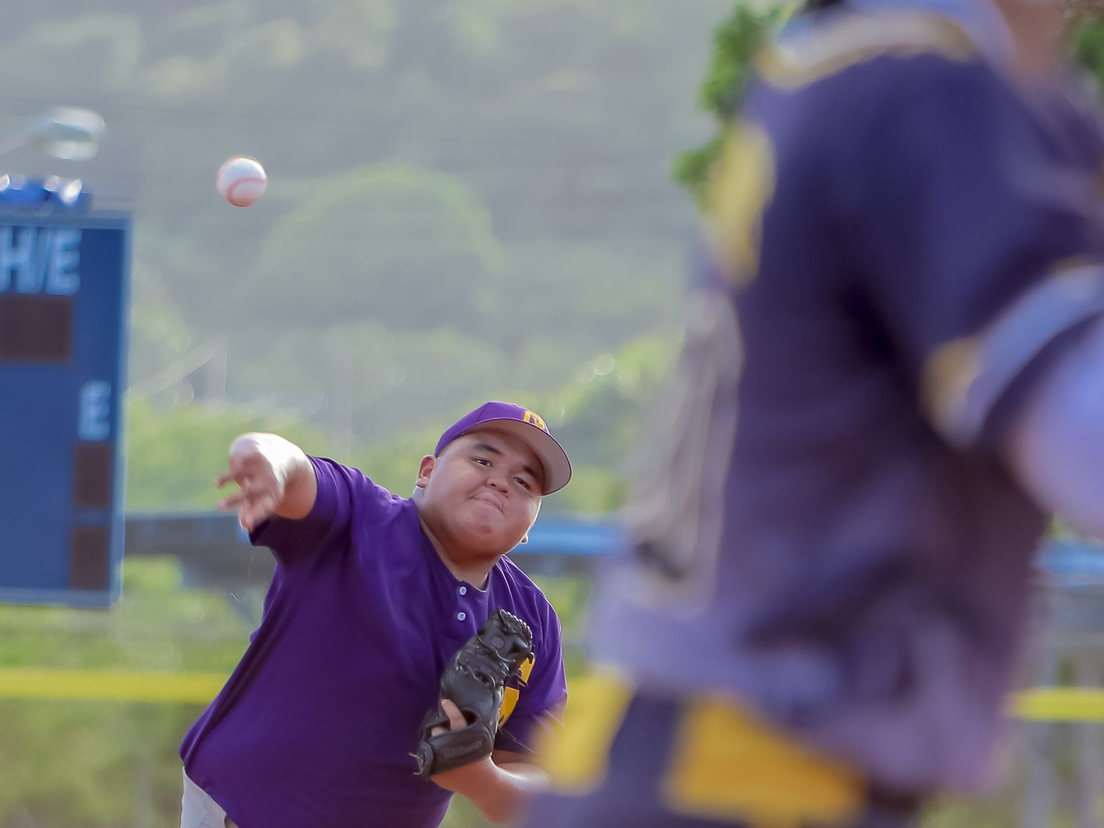 EJ Cali of George Washington High School throws a pitch against a Guam High batter.