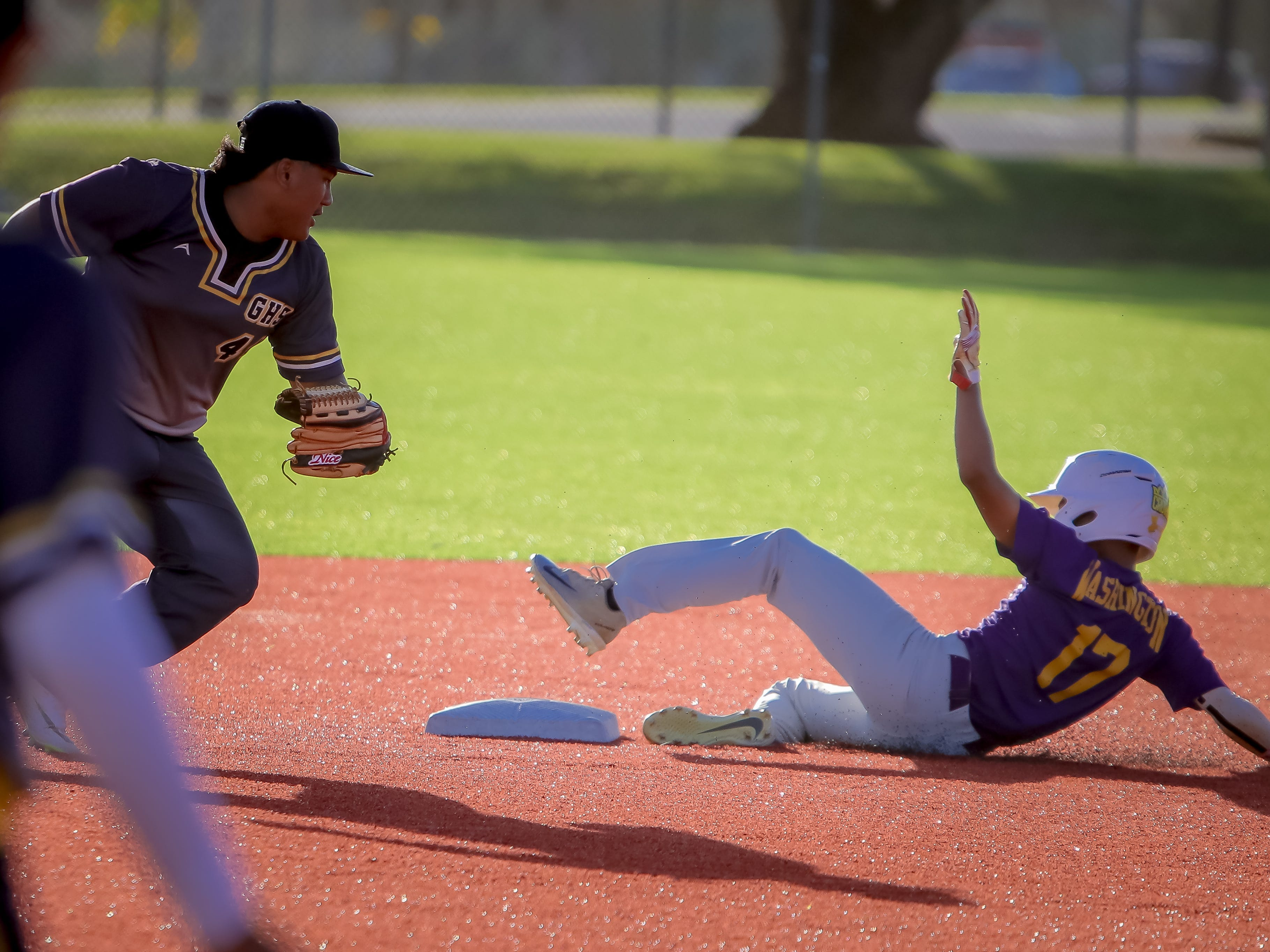 Cole Tenorio (17) of George Washington High School attempts to slide to second base.