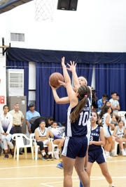 Action from the IIAAG girls basketball match between the St. Paul Christian School Warriors and Academy of Our Lady of Guam Cougars, held Nov. 13 at St. Paul. The Warriors won 66-37.