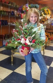 A fifth generation of the Shaw's Flowers family could be preparing for a future in floral design as Larry and Cindy Dixon's granddaughter Livia Ann Shaw Dixon, 7, displays a Christmas-themed arrangement she designed.