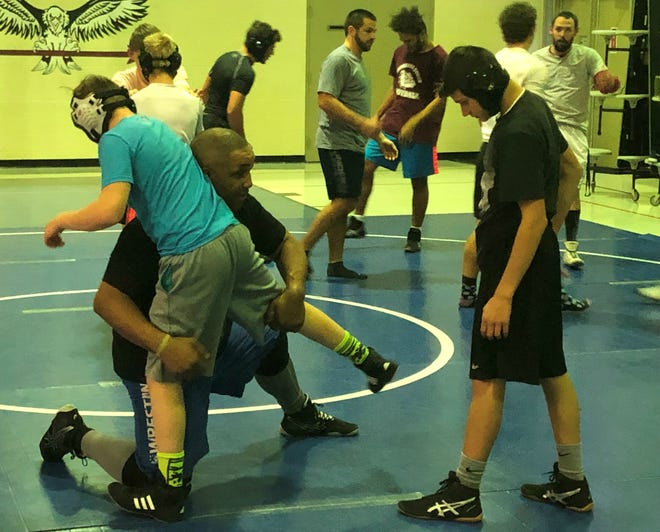 Henderson County coach Jermaine Poynter works with wrestlers Winston Young, left, and Aaron Williams during practice Tuesday at Central Learning Academy. Henderson County has formed high school and middle school wrestling programs that are competing for the first time this winter.