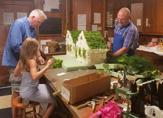 """Larry """"Pap"""" Dixon, right, is joined in preparing a floral set piece by granddaughter Livia Ann Shaw Dixon and Shaw's Flowers employee Neil Watson, who is both a designer and delivery man. The piece was a replica of a pair of houses for the funeral of a former homebuilder."""