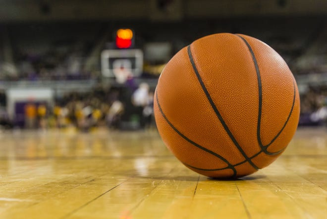 A basketball lies on the dusty hardwood court of a college hoops arena during a break in the action.