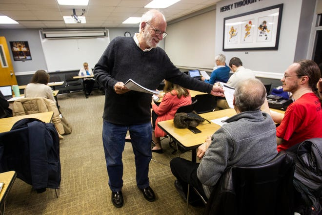 Jeff Cox, a University of Iowa history professor, hands a packet of information to Kenneth Elliott, Campaign to Organize Graduate Students vice president, before a panel on Tuesday, Nov. 13, 2018, at the Iowa Memorial Union in Iowa City.
