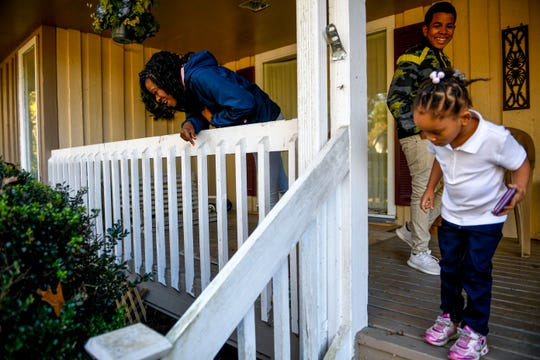 Sherrika Howard, left, and Jaliyah Allen, 4, right, laugh as their brother Cody Allen, 14, looks for a lost item underneath the porch at the home of Martha Epperson in Jackson, Tenn., on Wednesday, Nov. 7, 2018.