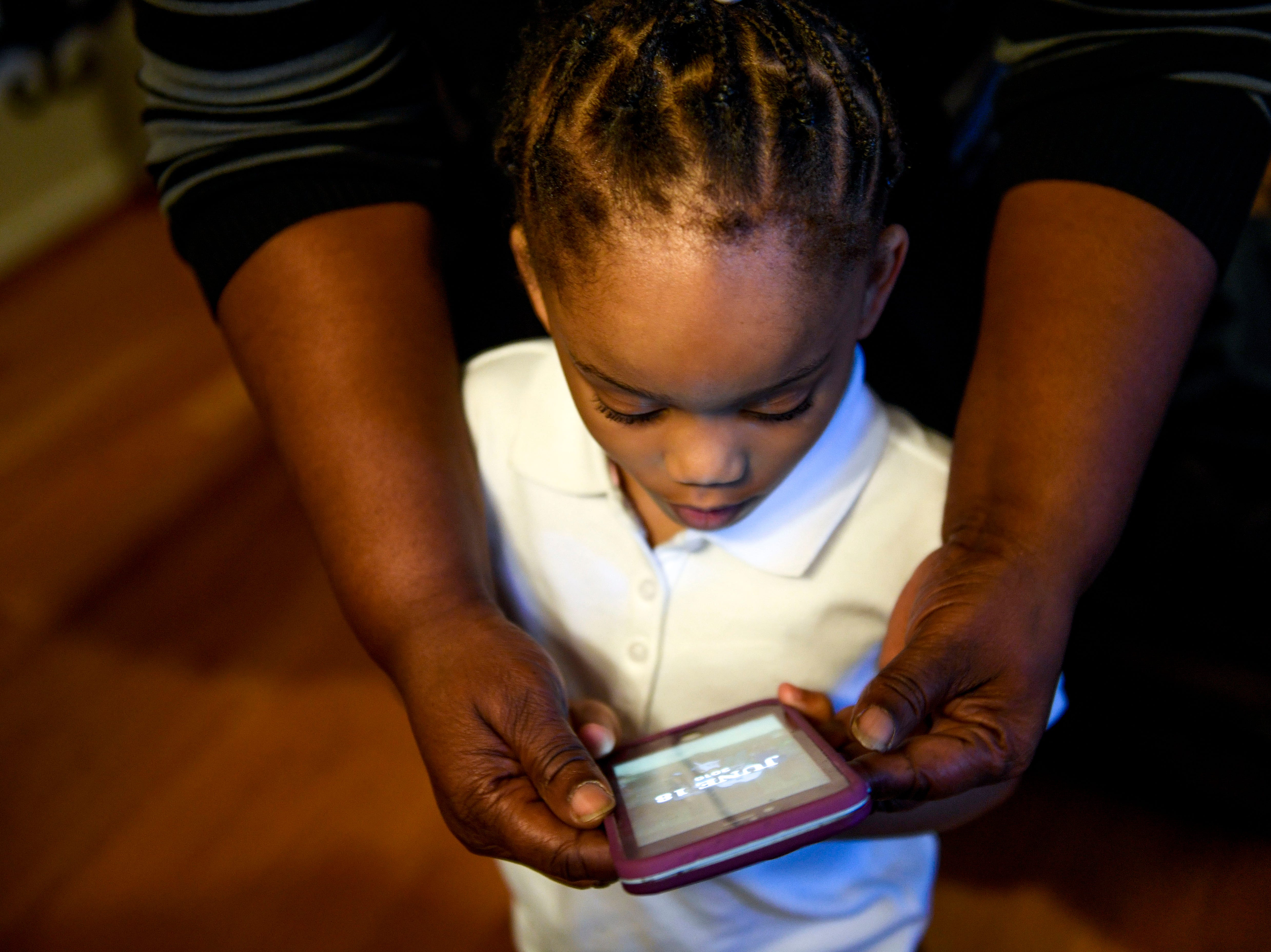 Jaliyah Allen, 4, is helped with a cell phone by Martha Epperson at the home of Martha Epperson in Jackson, Tenn., on Wednesday, Nov. 7, 2018.