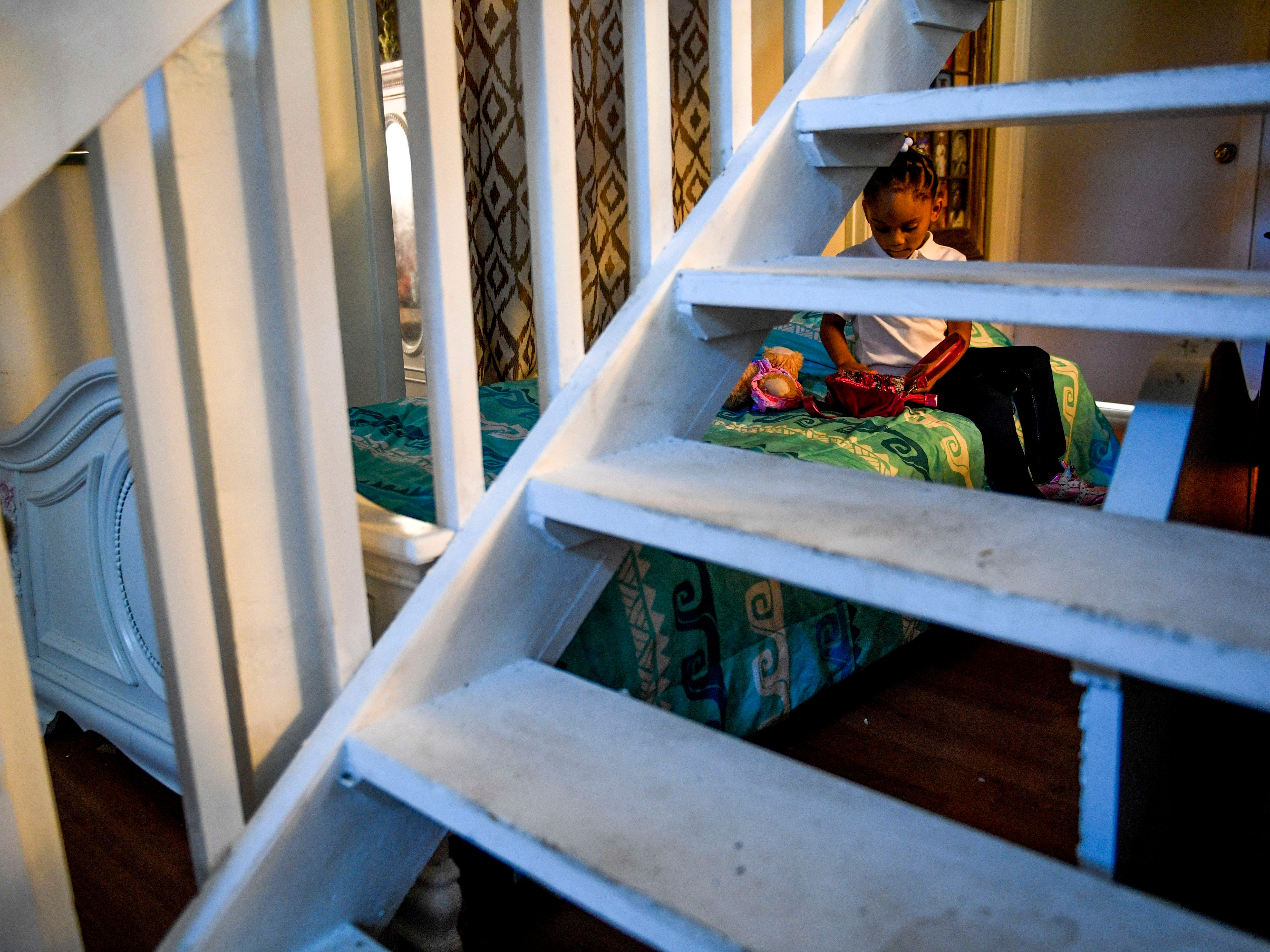 Jaliyah Allen plays with toys while sitting on a spare bed for guests tucked behind the stairs at the home of Martha Epperson in Jackson, Tenn., on Wednesday, Nov. 7, 2018.