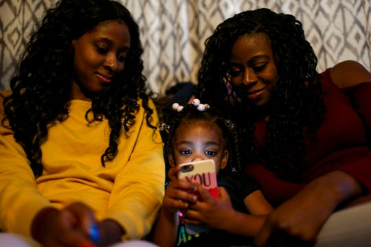 Sherrika Howard, right, and Maya Kemp, left, lean in and watch Peyton Howard, 2, play on a cell phone at the home of Martha Epperson in Jackson, Tenn., on Wednesday, Nov. 7, 2018.